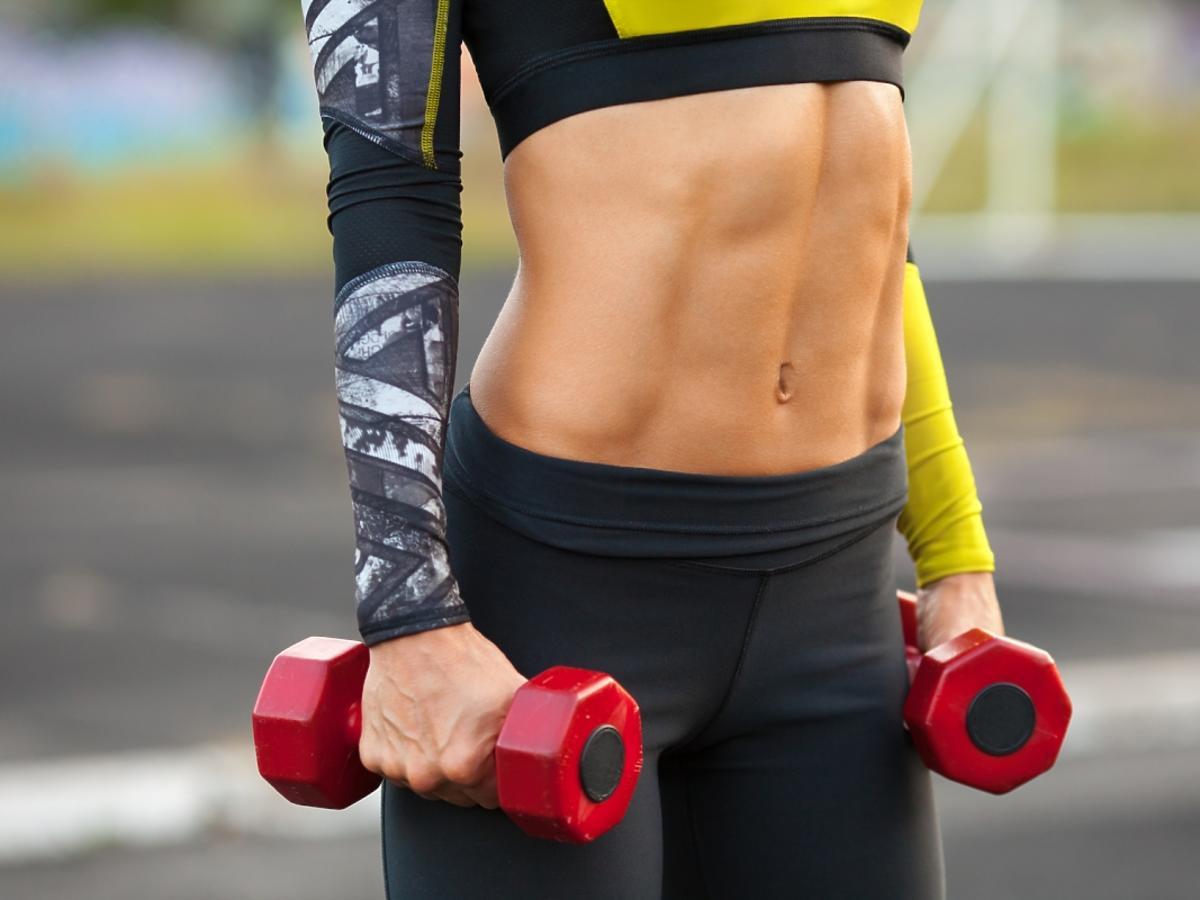 Kobieta pokazuje mięśnie brzucha