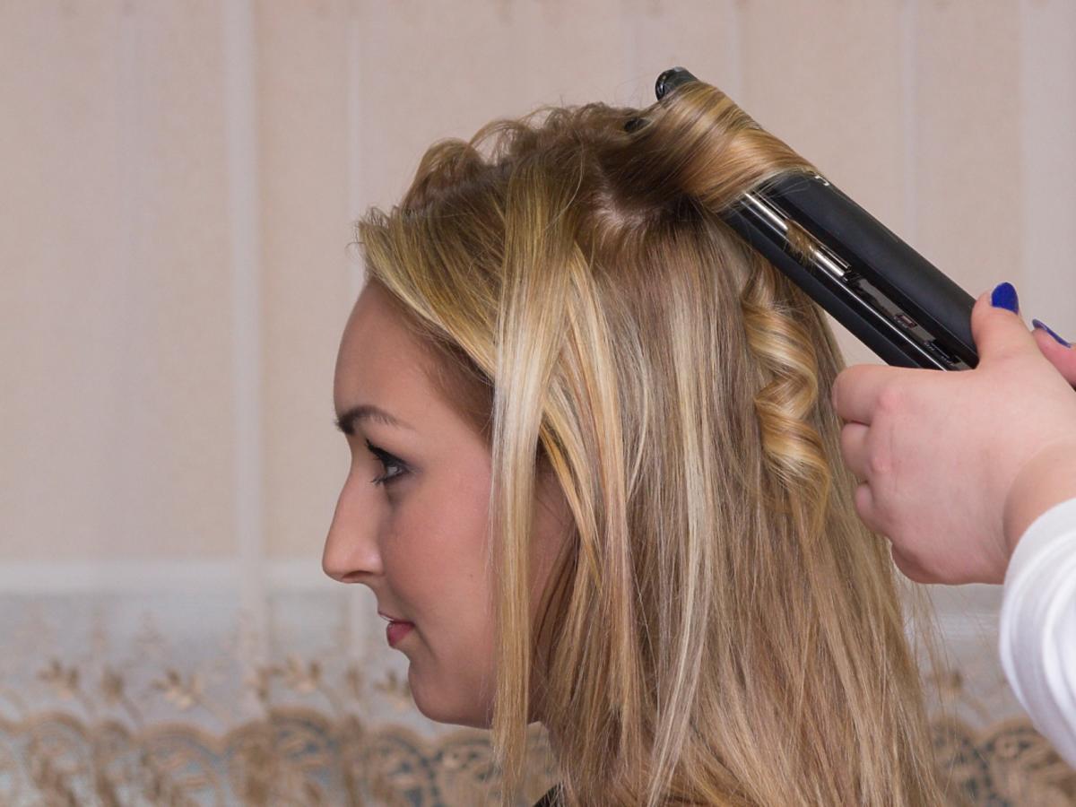 Kobieta prostuje blondynce włosy
