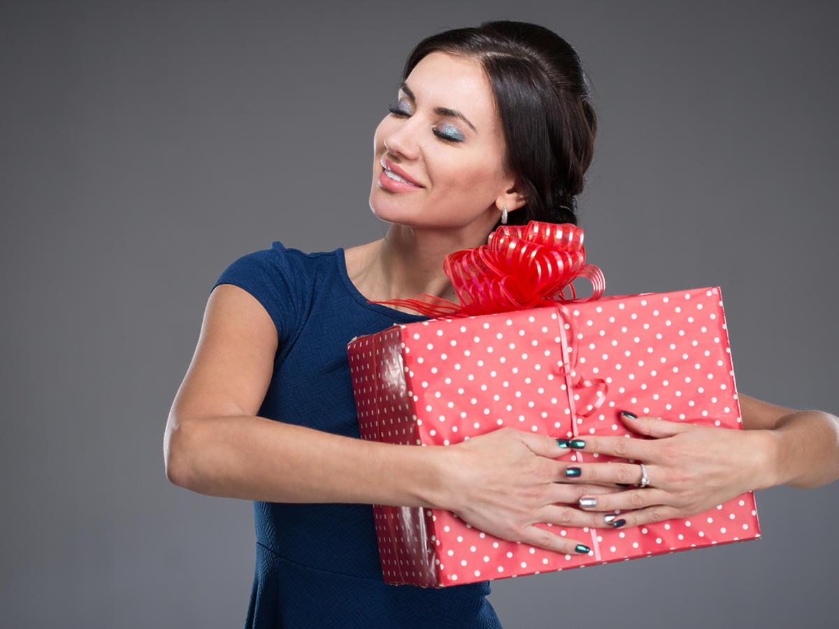 Kobieta przytula pudło z prezentem.