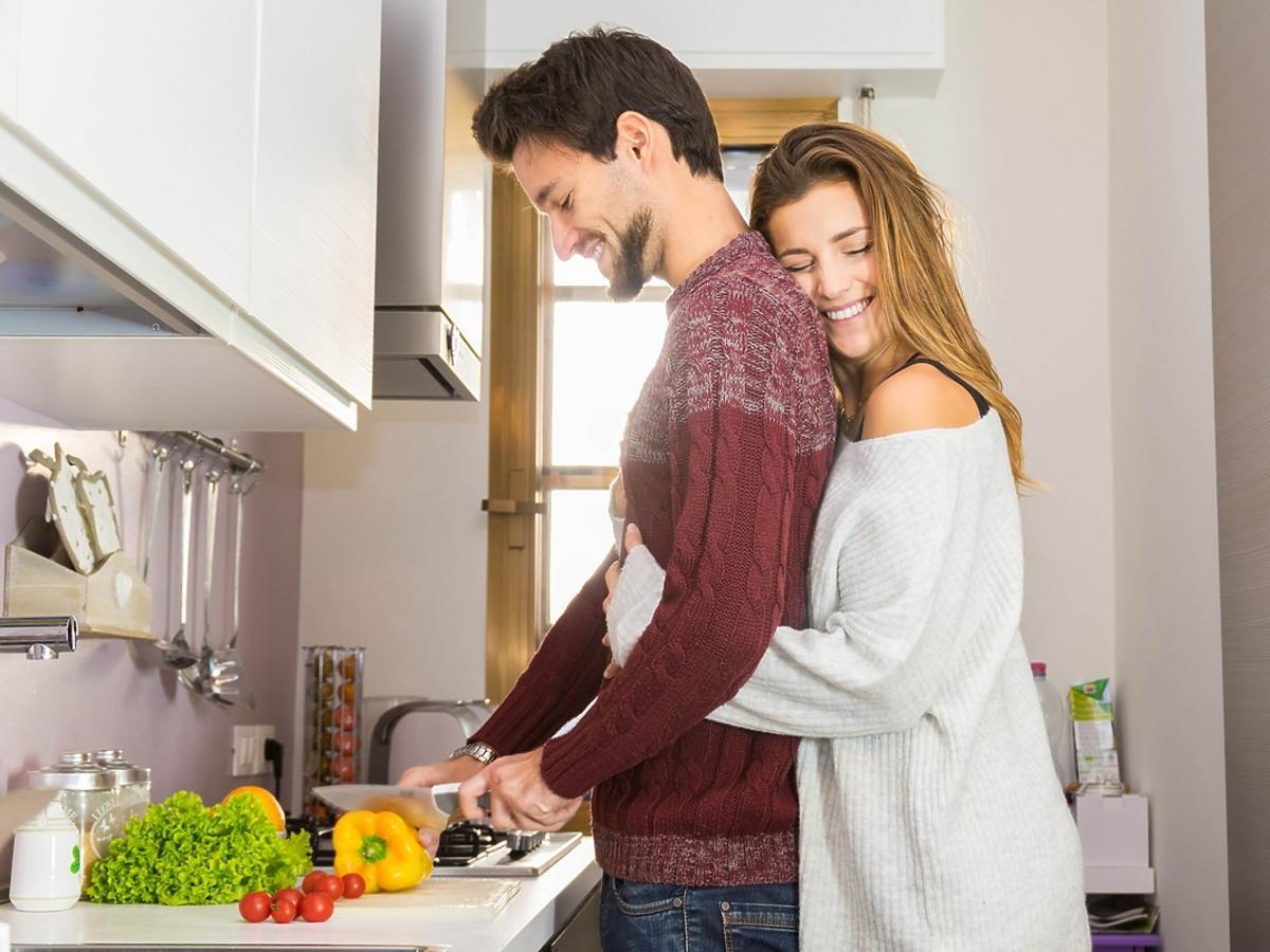 Kobieta przytula swojego męża, który przygotowuje śniadanie.