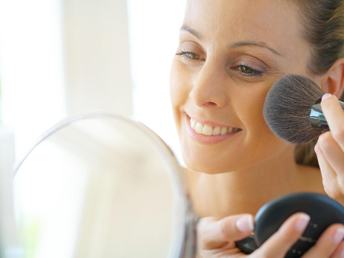 kobieta pudrująca się patrzy się w lustro