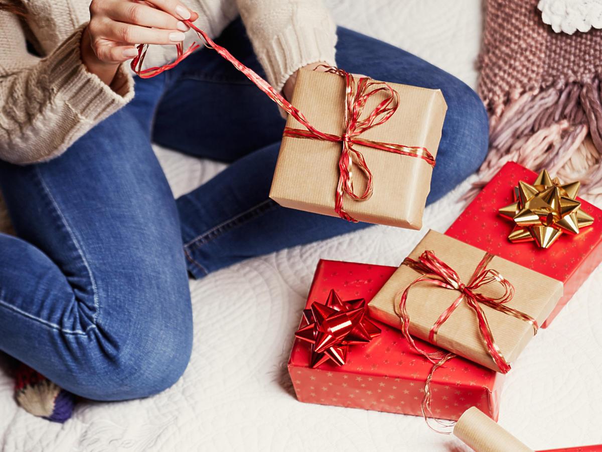 Kobieta rozpakowuje świąteczne prezenty.