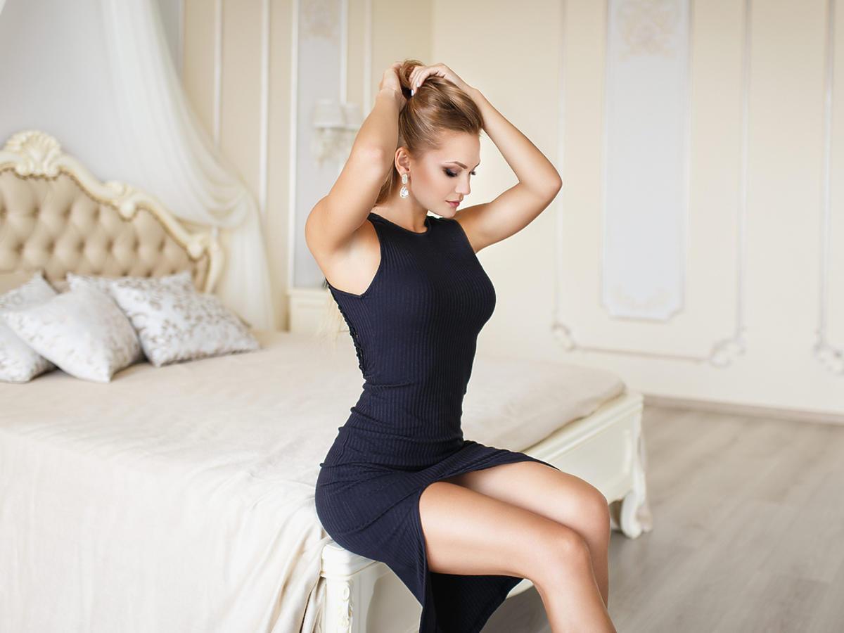 kobieta siedząca na łóżku w granatowej koktajlowej sukience