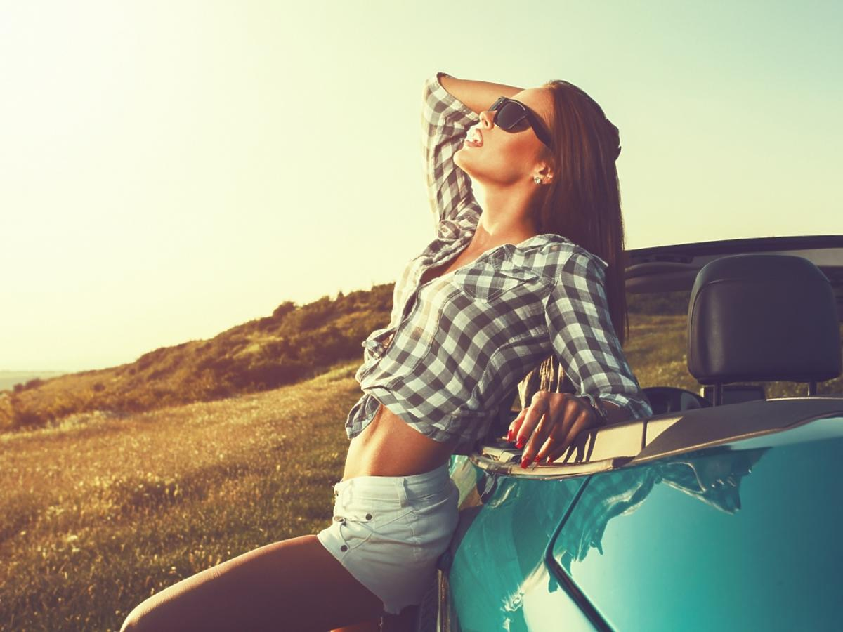 Kobieta siedząca na masce samochodu
