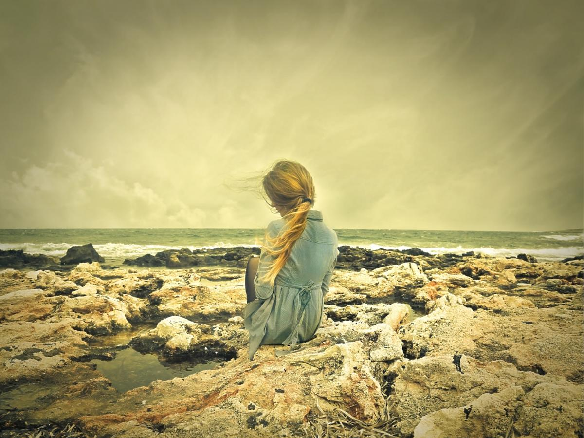 kobieta siedząca na wybrzeżu