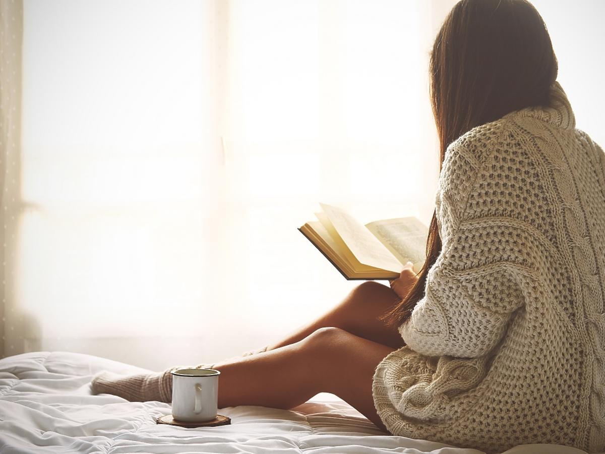 Kobieta siedząca tyłem czyta książkę