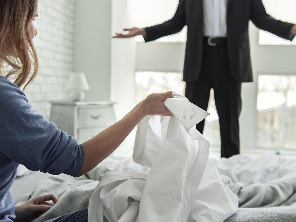 Kobieta siedzi na łóżku i kłóci się z mężem.