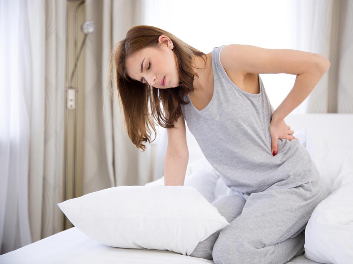 Kobieta siedzi na łóżku i trzyma się za plecy