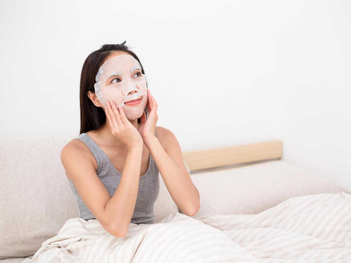 Kobieta siedzi na łóżku, na twarzy ma maseczkę w płachcie.
