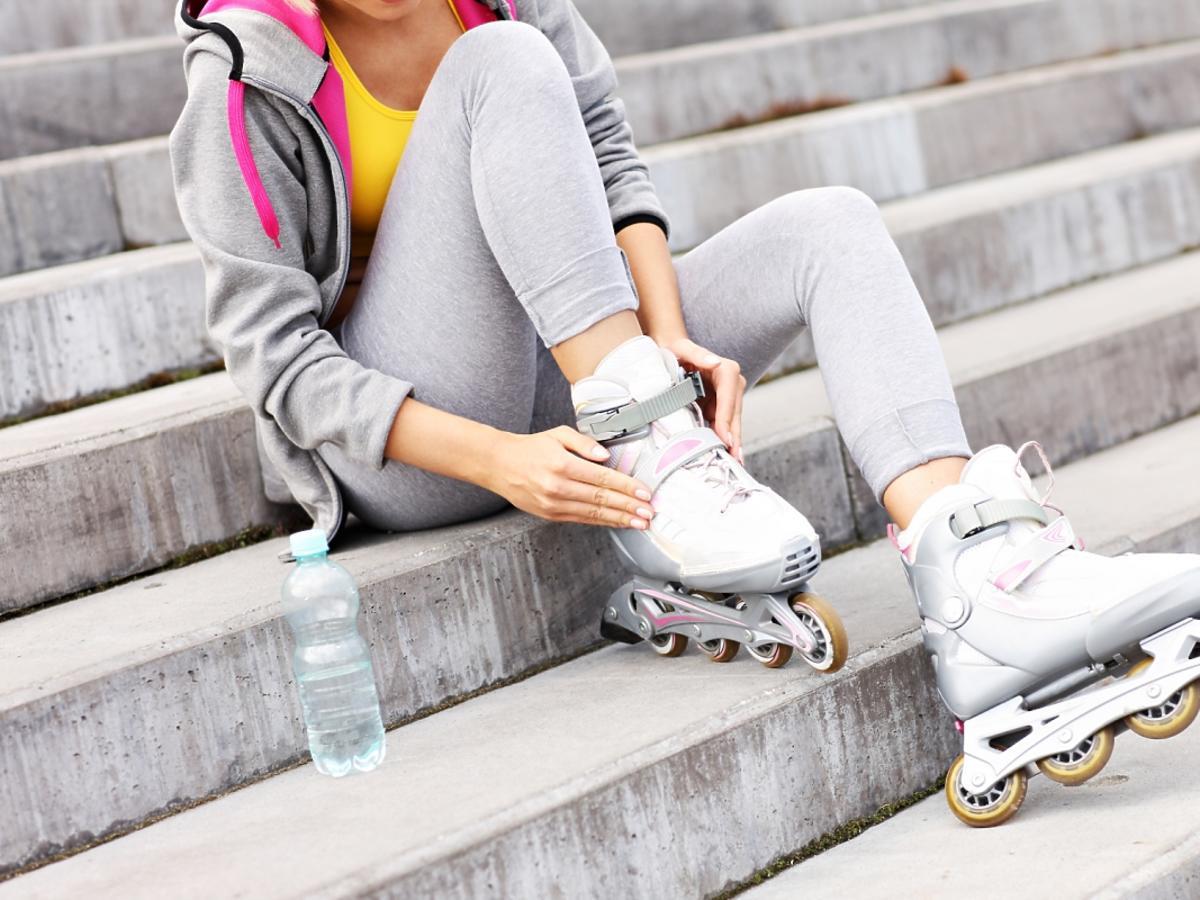 Kobieta siedzi na schodach i zakłada rolki.