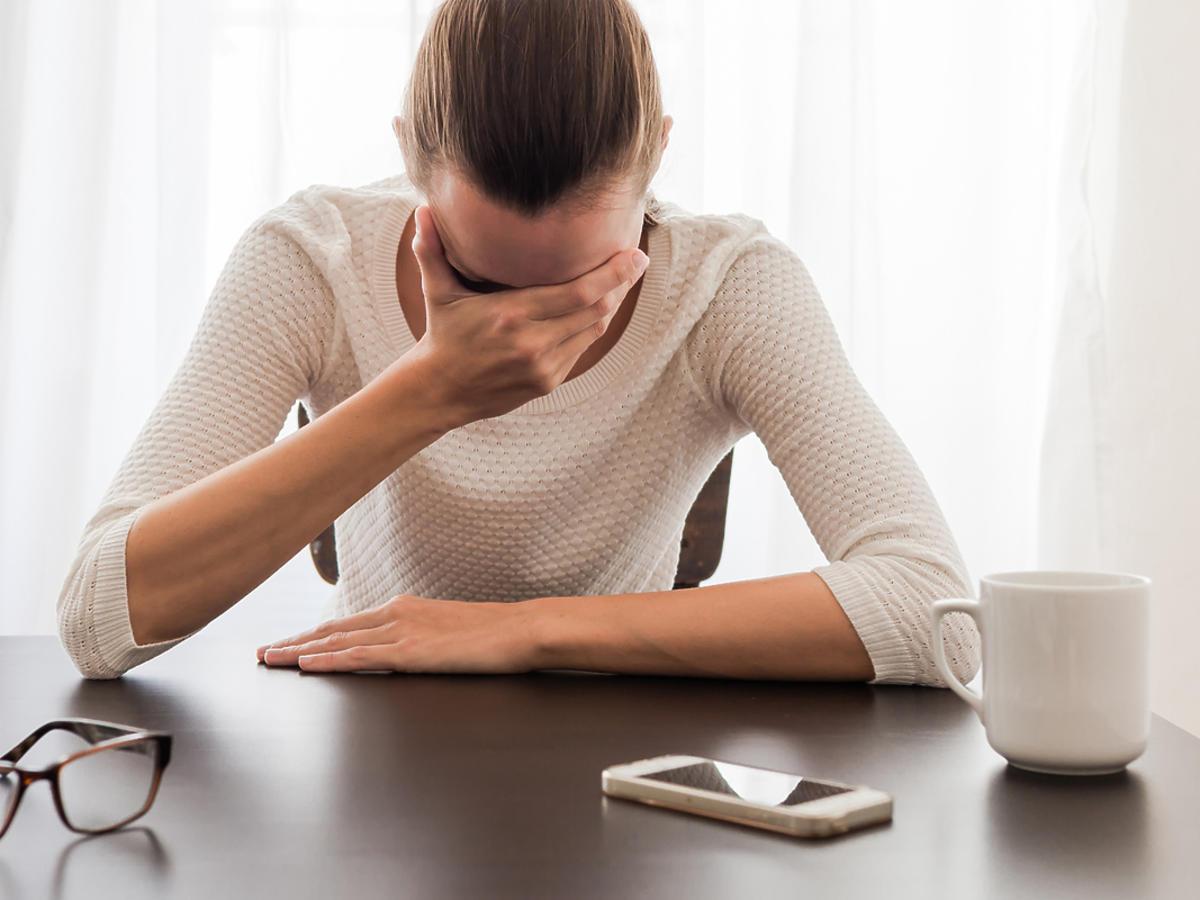 Kobieta siedzi przy stole z głową zakrytą dłońmi. Wygląda na załamaną. Przed nią leży telefon i filiżanka.