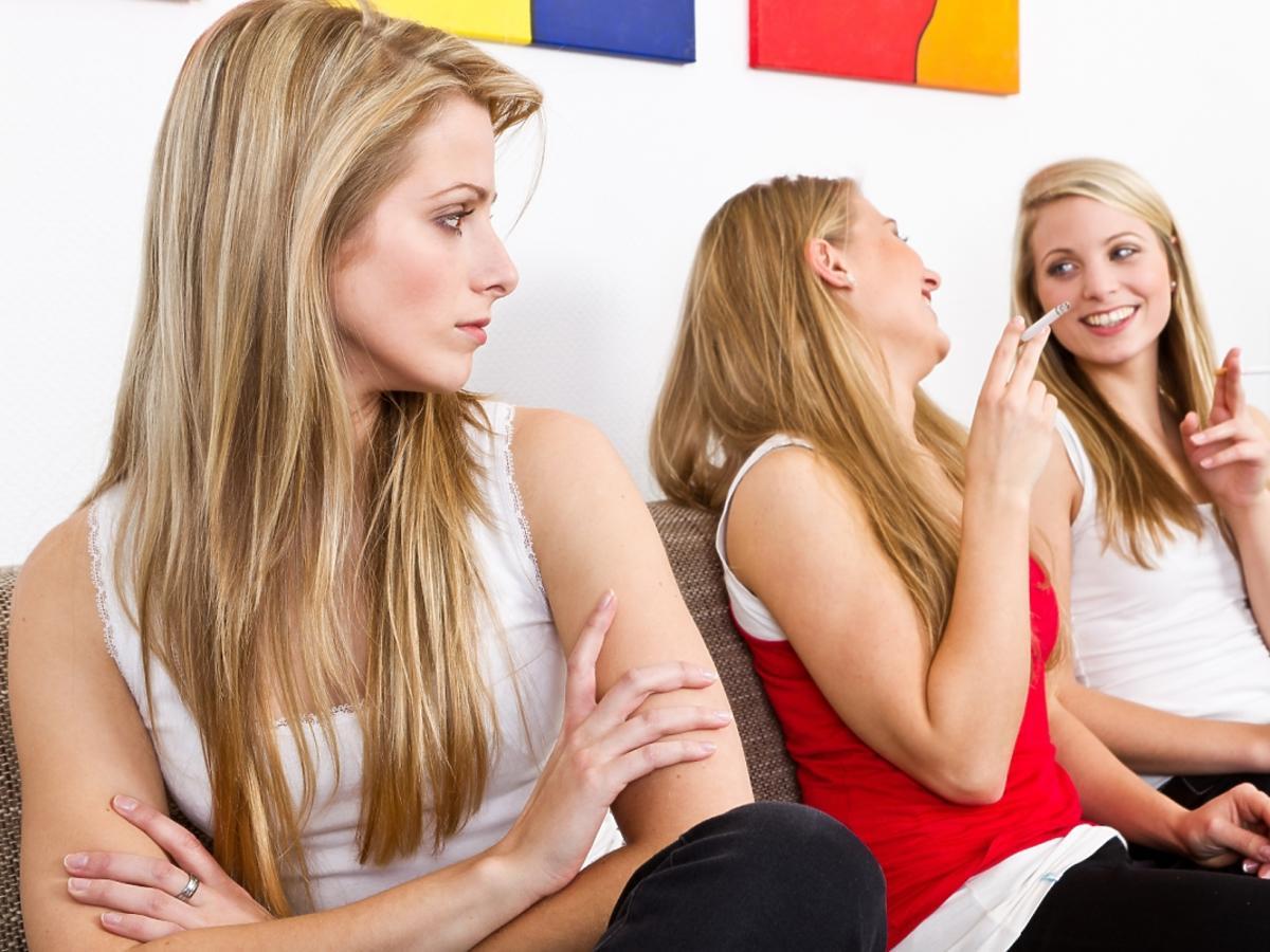 Kobieta siedzi w towarzystwie palaczy