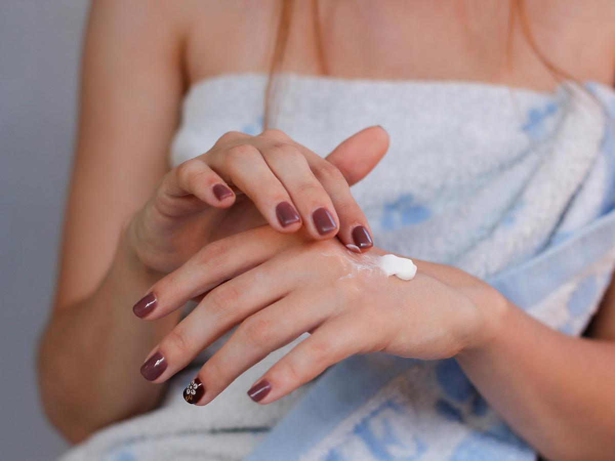 Kobieta smaruje dłoń leczniczą maścią.