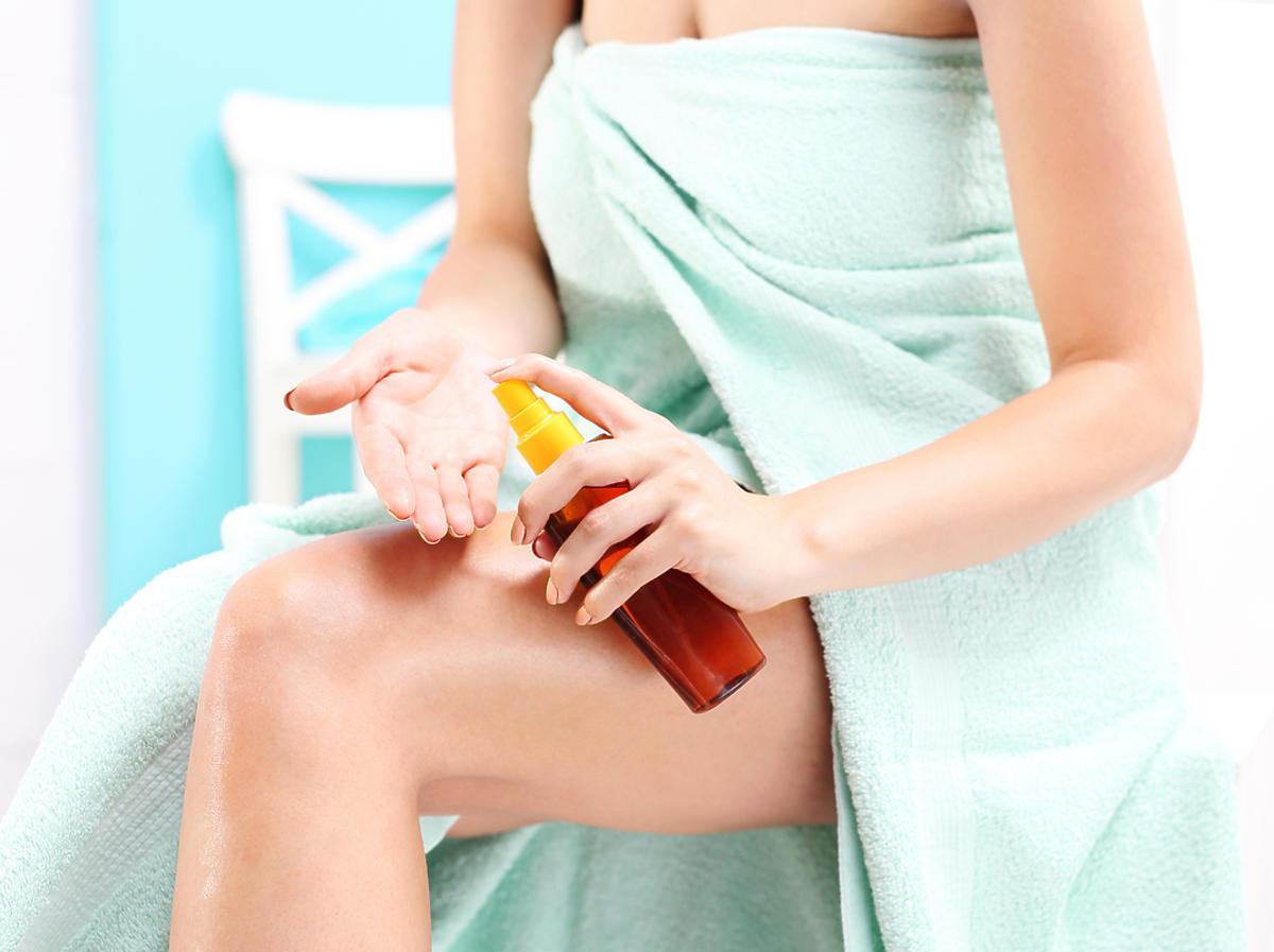 Kobieta smaruje nogi olejkiem do ciała
