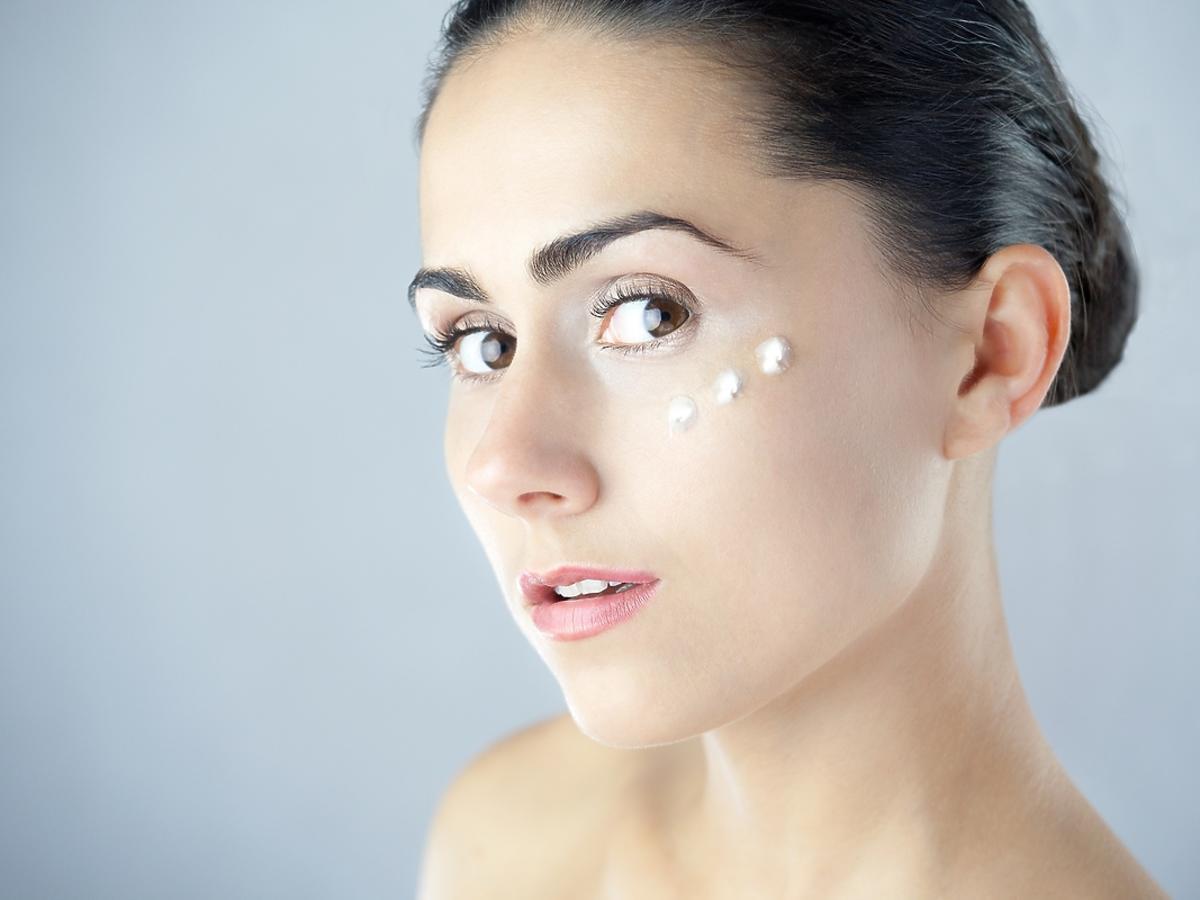 Kobieta smaruje się kremem pielęgnacyjnym do twarzy.