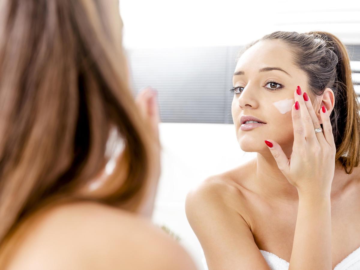 Kobieta smaruje się w łazience kremem do twarzy.