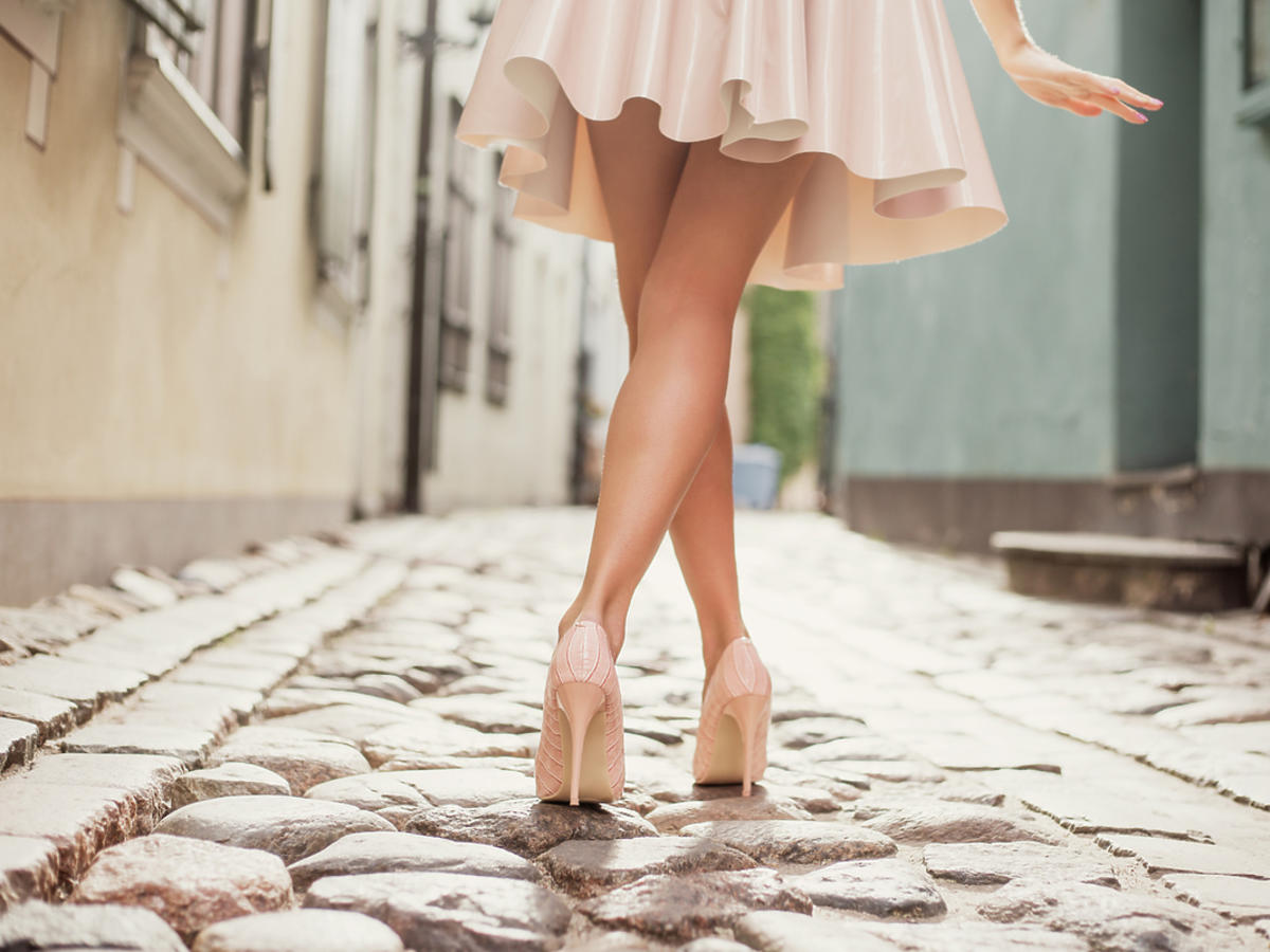 Kobieta spaceruje w szpilkach i różowej spódnicy do kolan.