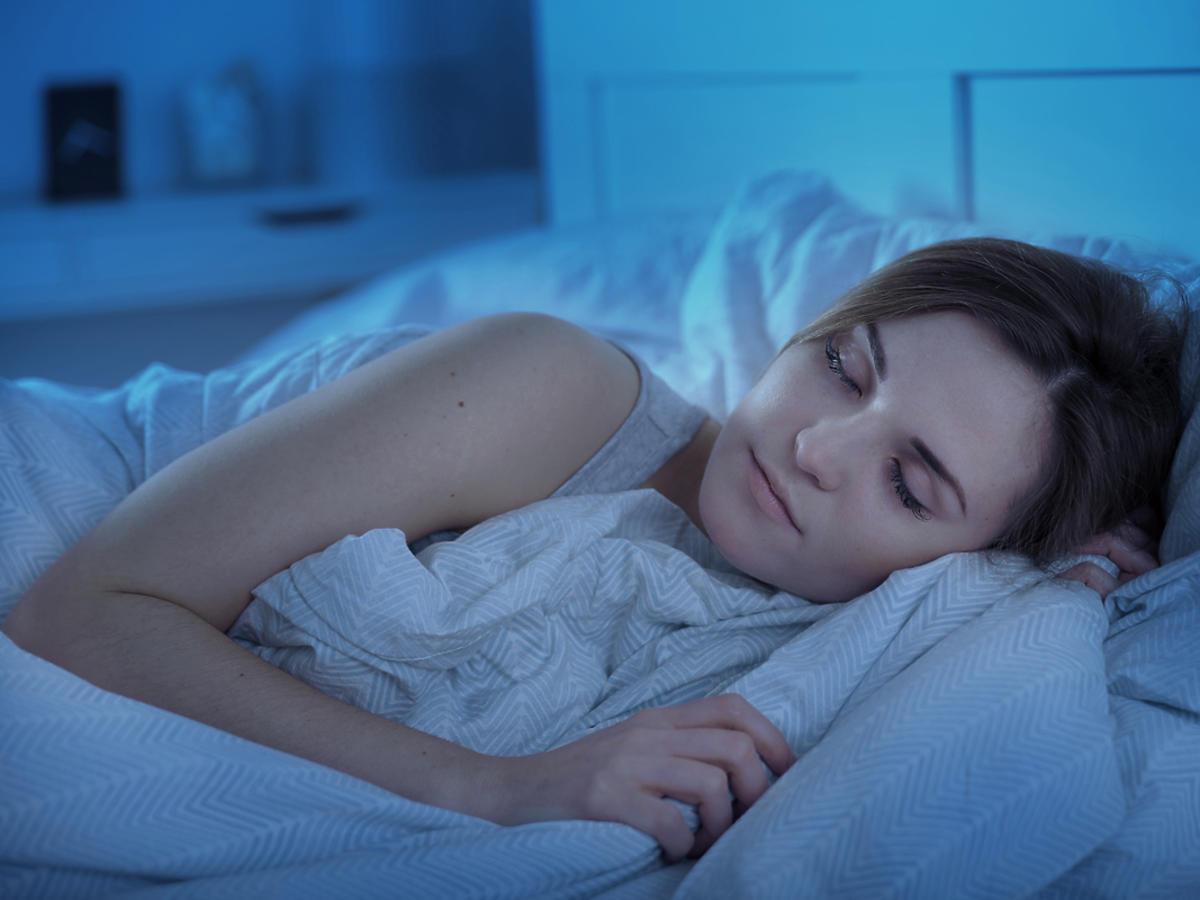 Kobieta śpi w łóżku.