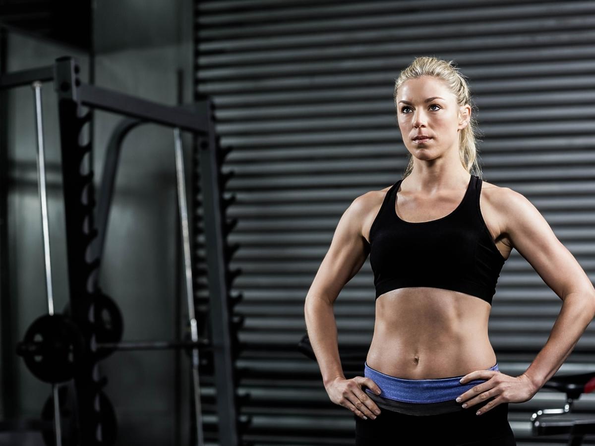 Kobieta stoi na siłowni.