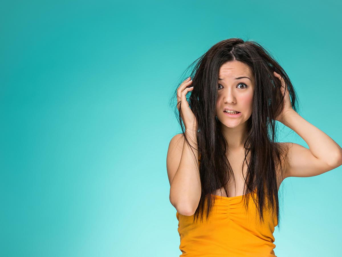 Kobieta stoi pod niebieską ścianą i trzyma się za głowę, ma bardzo zniszczone włosy.