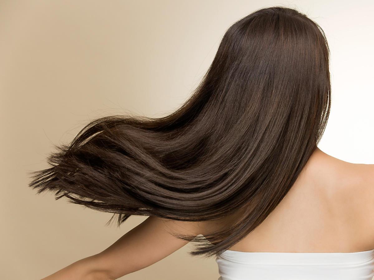 Kobieta stoi tyłem do widza, ma długie, ciemne, rozwiane włosy.