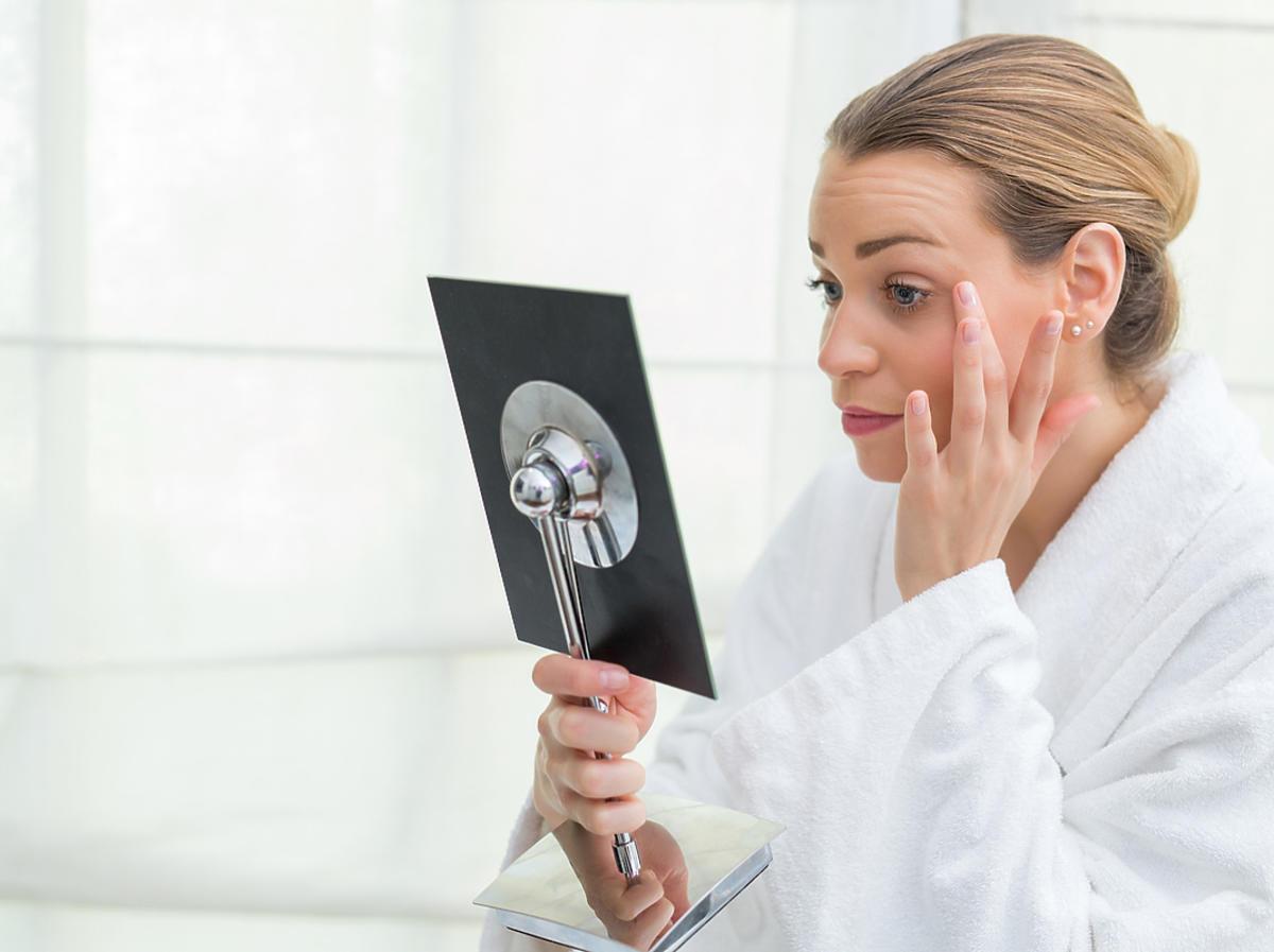 kobieta stojąca przed lustrem i oglądająca swoją twarz