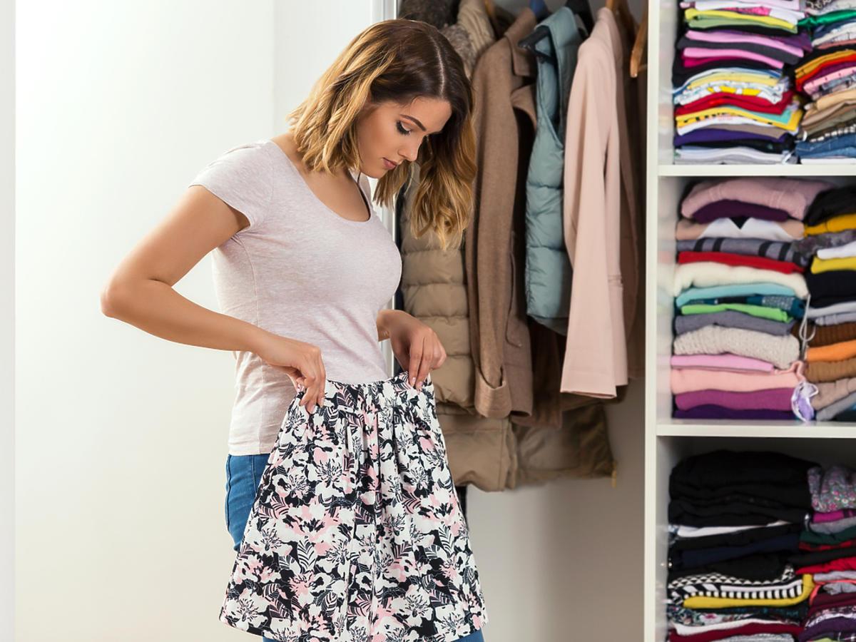 kobieta stojąca przed szafą ze spódnicą w ręku