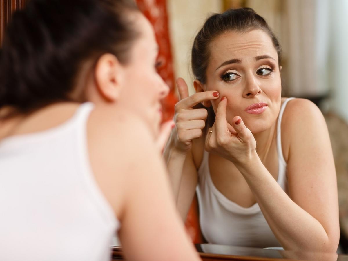 Kobieta stojąca przy lustrze