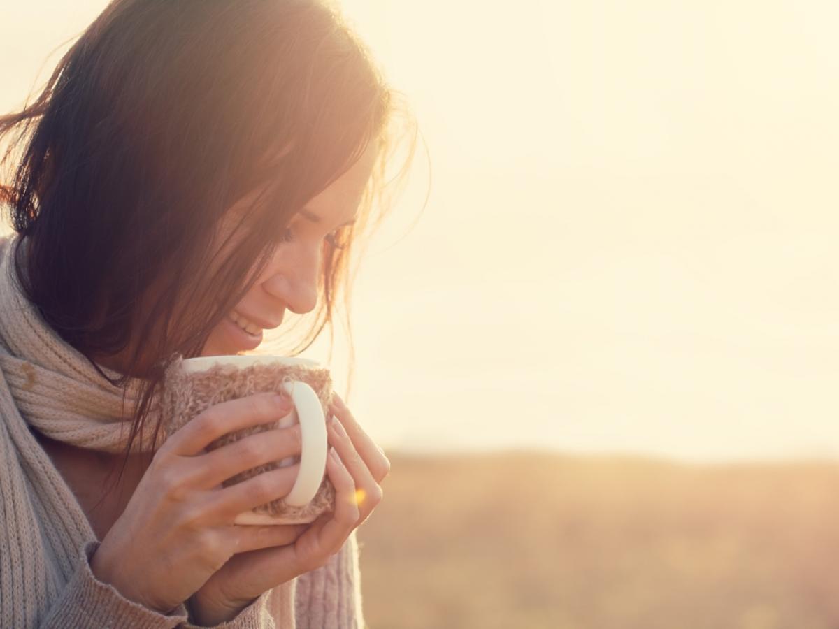 kobieta trzyma kubek gorącego napoju