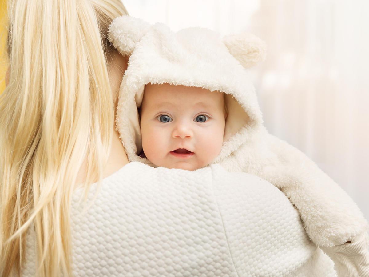 Kobieta trzyma na rękach niemowlę.