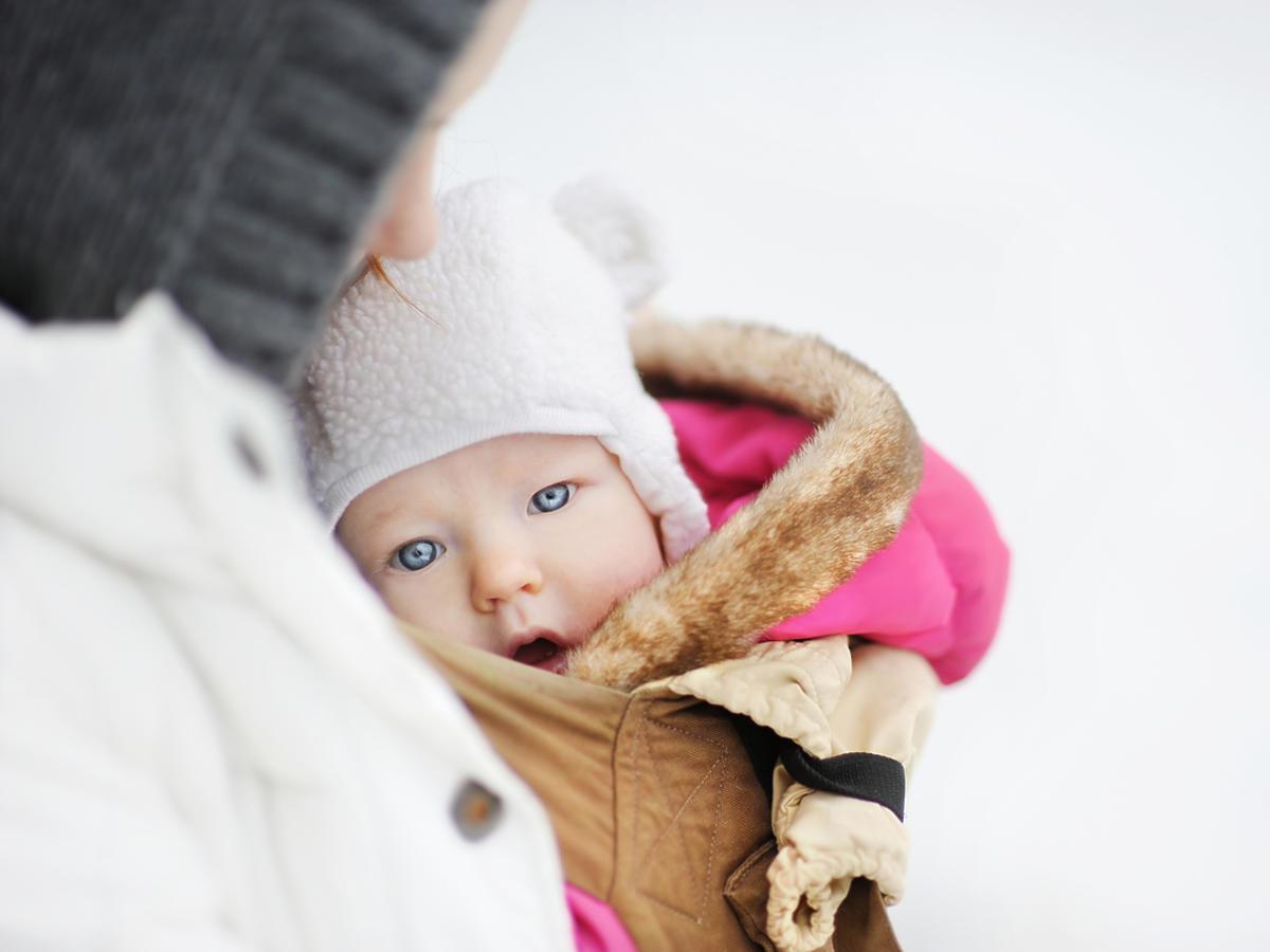 Kobieta trzyma na rękach ubranego w zimowy kombinezon noworodka.