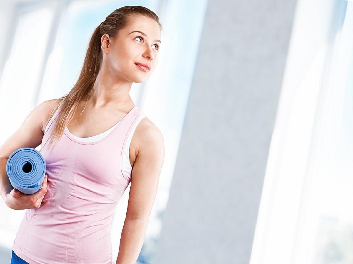 kobieta trzyma pod pachą matę do ćwiczeń