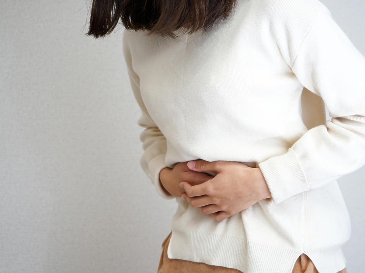 Kobieta trzyma się za brzuch.