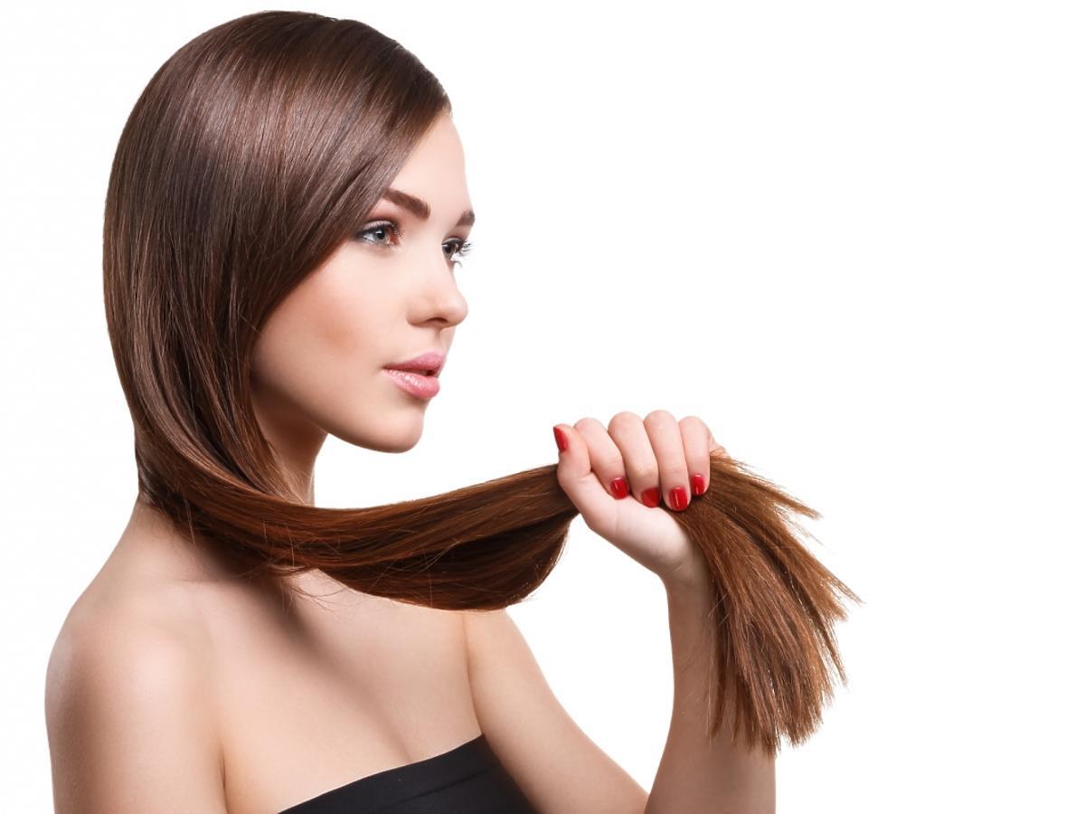 Kobieta trzyma w dłoni swoje grube włosy