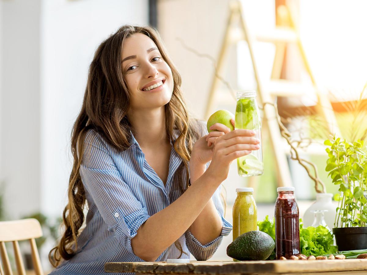 kobieta-trzymająca jabłko i butelkę