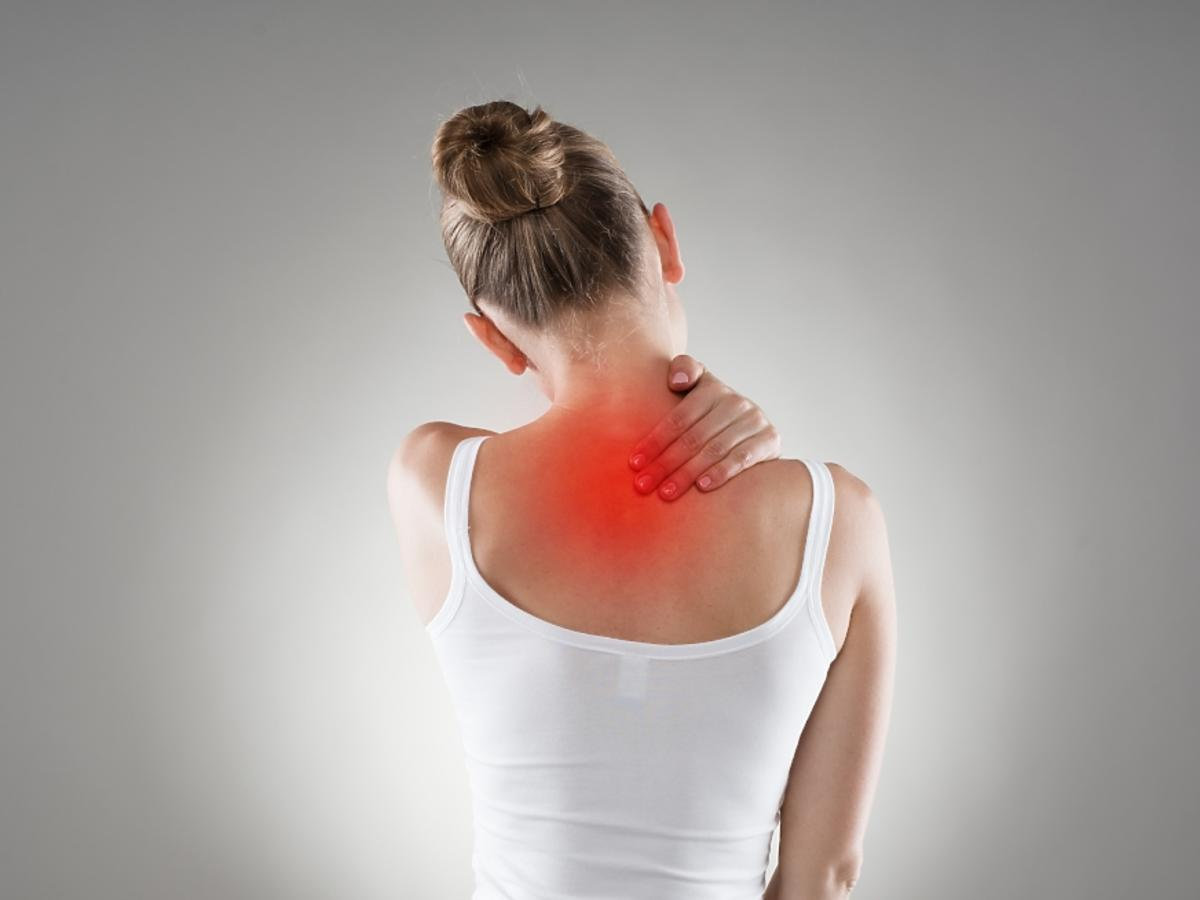 kobieta trzymająca się za bolący kark