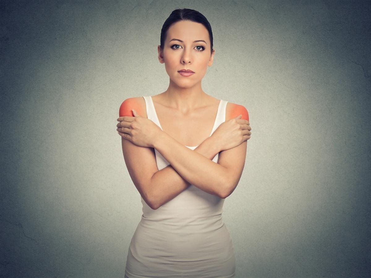 kobieta trzymająca się za ramiona