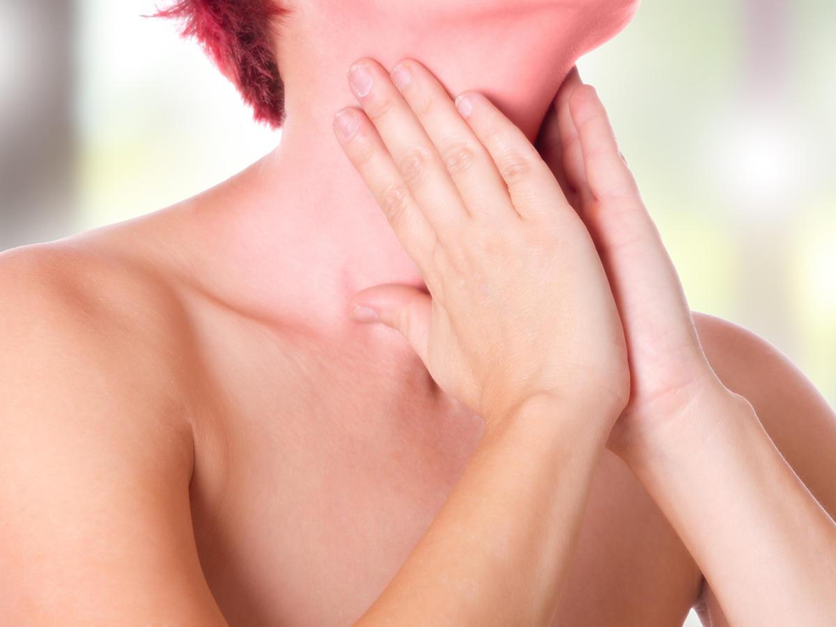 kobieta trzymająca się za szyję