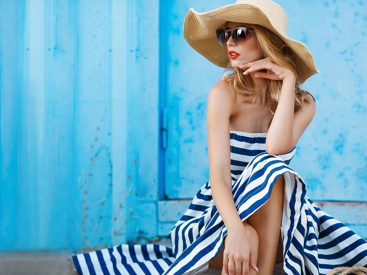 Kobieta ubrana w letnią sukienkę siedzi na schodach.