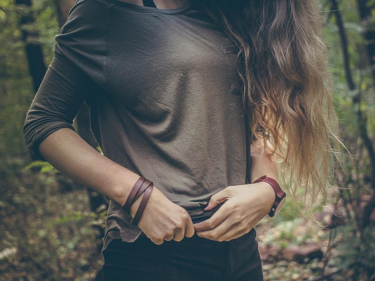 Kobieta w beżowym swetrze. Zbliżenie na talię.