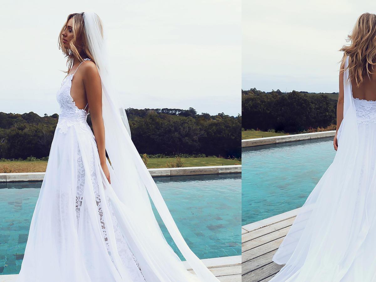 Kobieta w białej koronkowej sukni ślubnej z tiulem nad jeziorem
