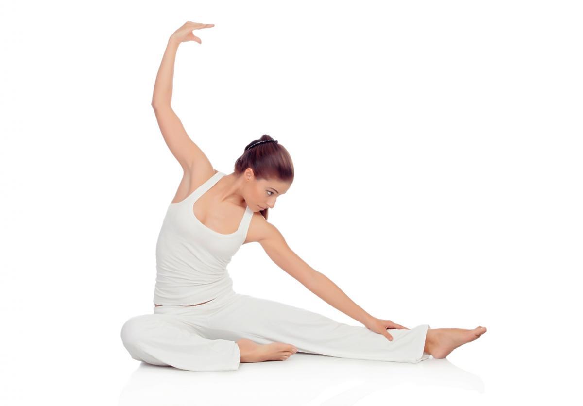 Kobieta w białym stroju wykonuje ćwiczenia pilatesu.