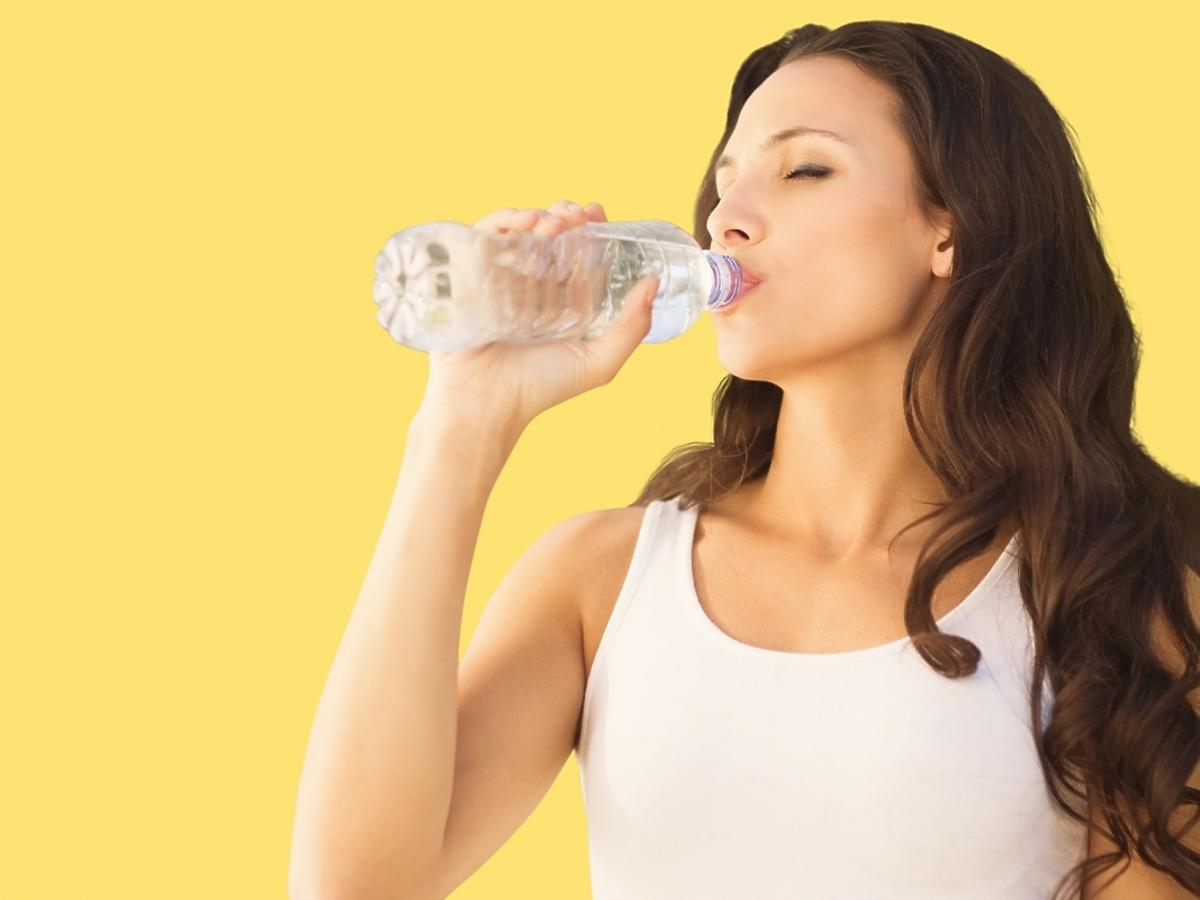Kobieta w białym topie pije wodę z butelki.