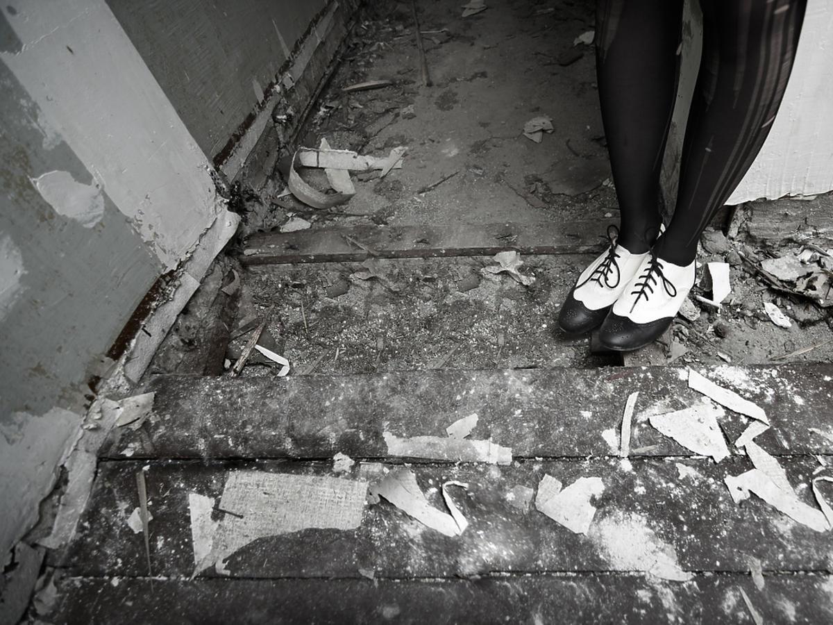 Kobieta w butach typu oxford stoi pod ścianą.