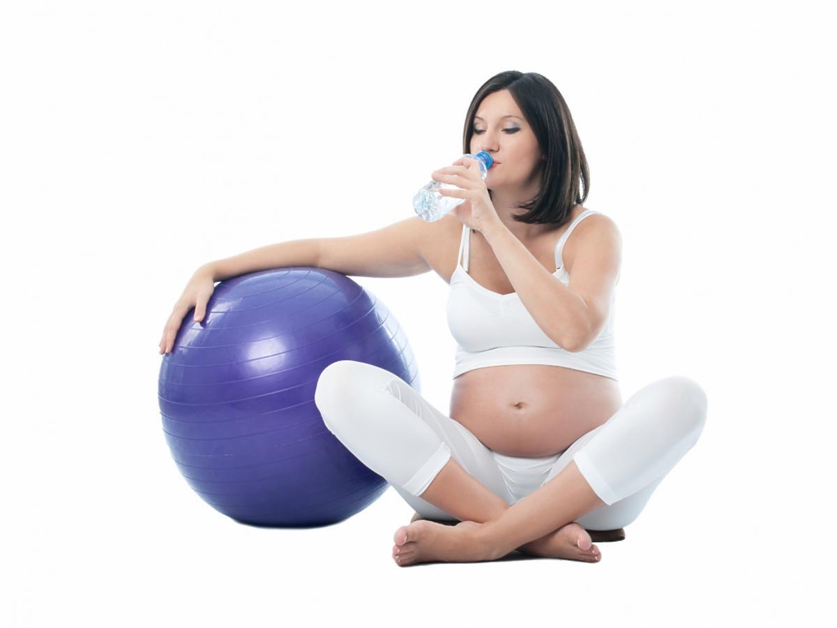 kobieta w ciąży siedzi obok piłki gimnastycznej