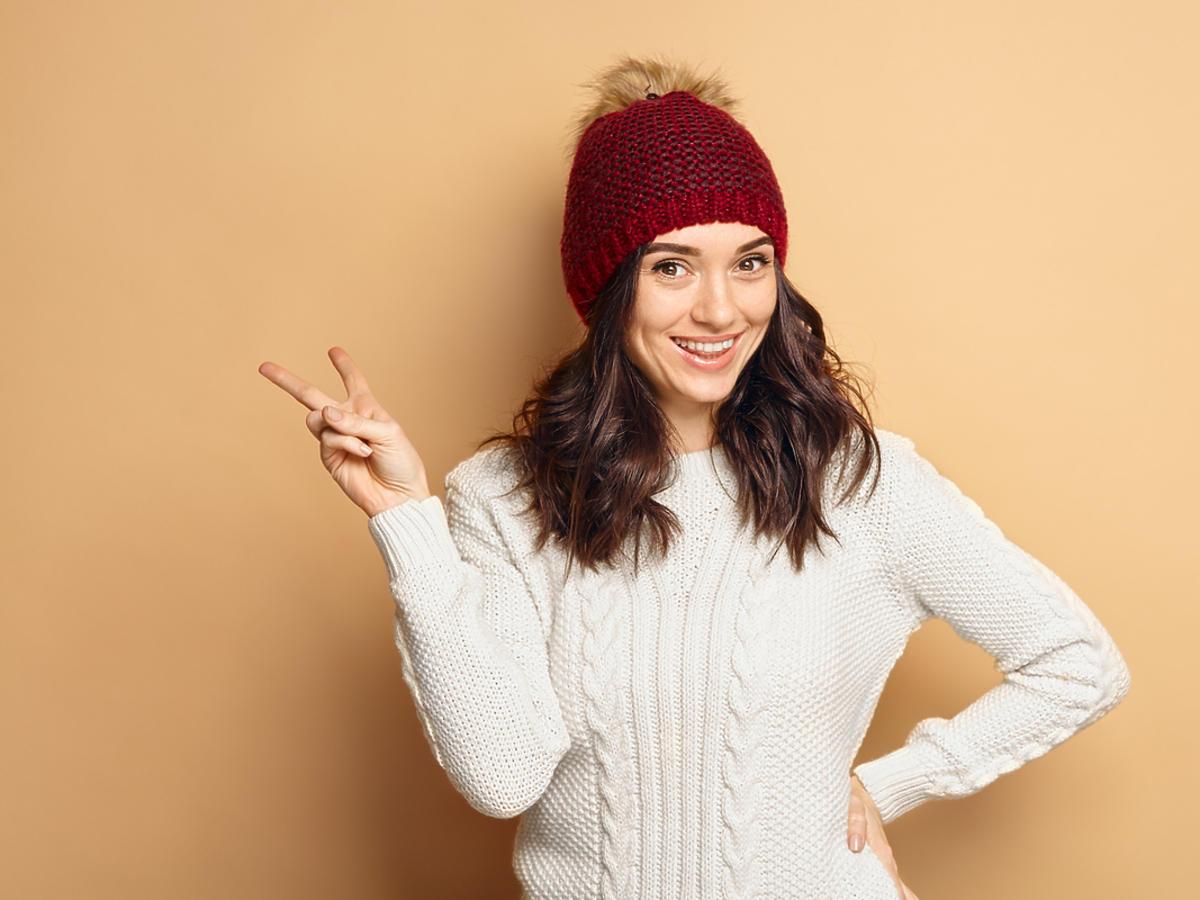 Kobieta w czapce uśmiecha się.