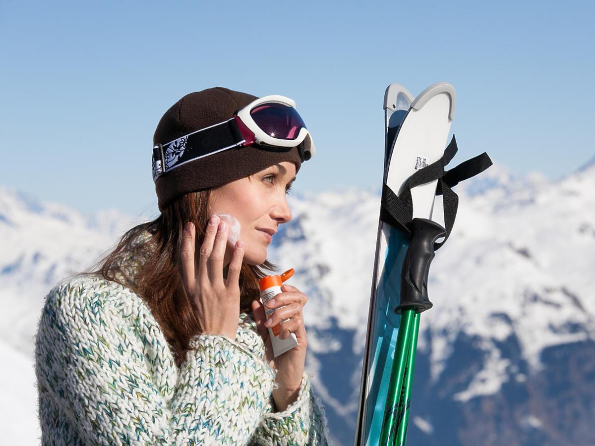 kobieta w górach smaruje twarz kremem i trzyma narty