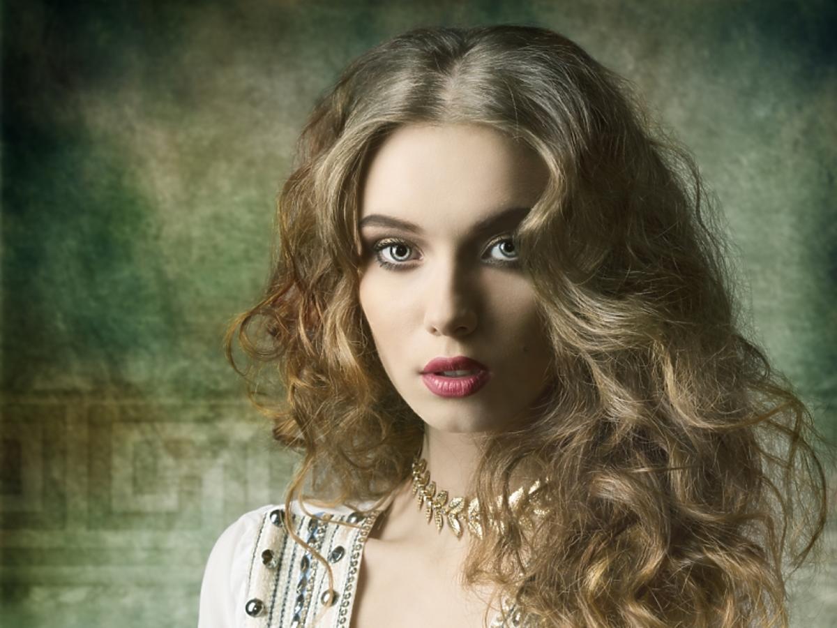 Kobieta w jasnej, zdobionej tunice i falowanych włosach