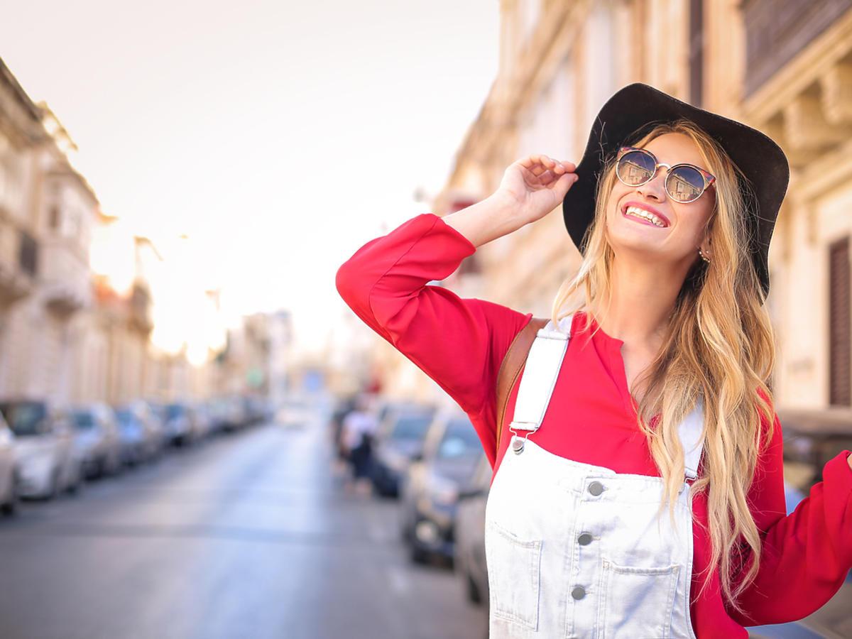 kobieta w jasnych spodniach ogrodniczkach i kapeluszu