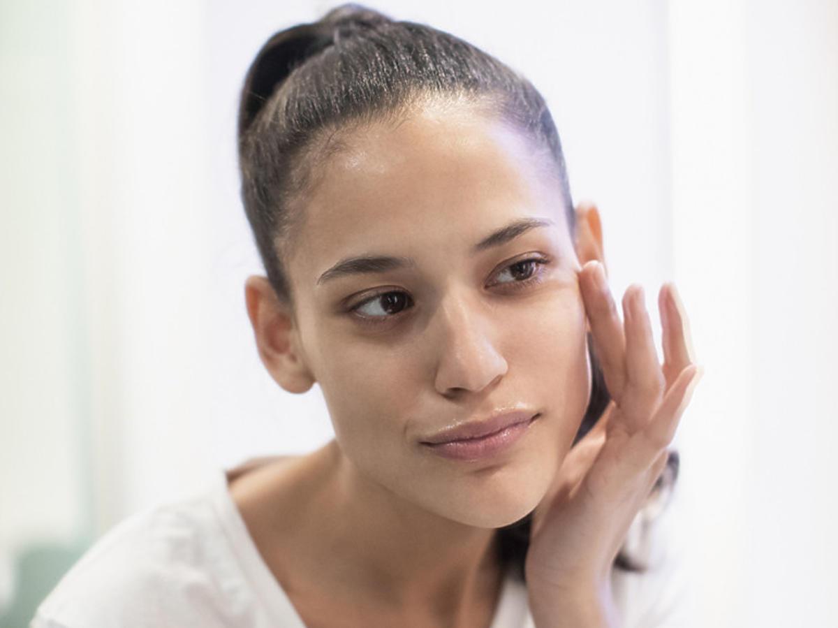 Kobieta w łazience z kremem do twarzy